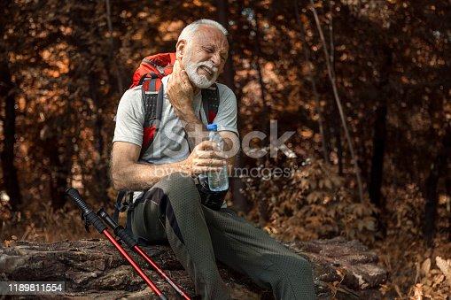 Senior man hiking taking a break drinking water