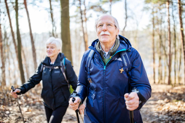 Senior man hiking with friend Retired senior man walking in front with a woman behind on a forest trail. Elderly people on a country walk. nordic walking stock pictures, royalty-free photos & images
