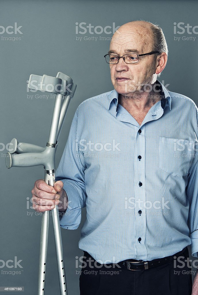 Senior man hold a pair of crutches and looks sceptical stock photo