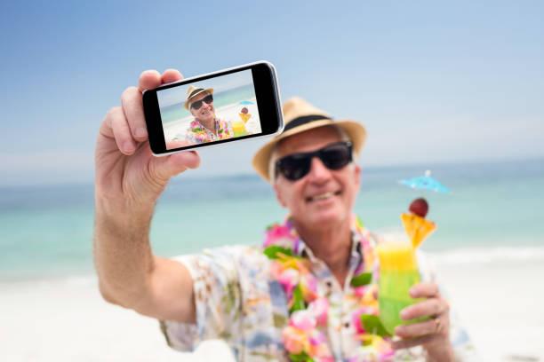 senior woman holding ein cocktailglas und nehmen ein selbstporträt - senior bilder wasser stock-fotos und bilder