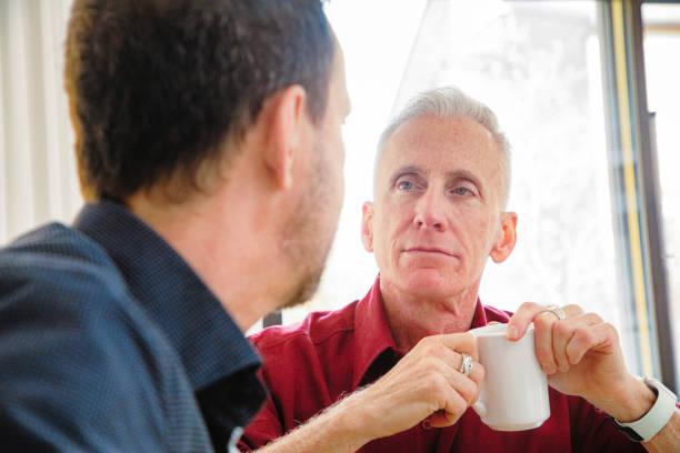 Senior Mann hält eine Kaffeetasse mit einem ernsthaften Gespräch – Foto