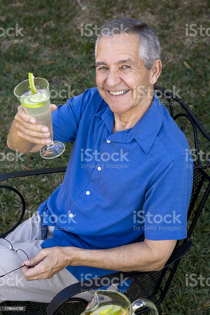Senior man holding a glass of lemonade royalty-free stock photo