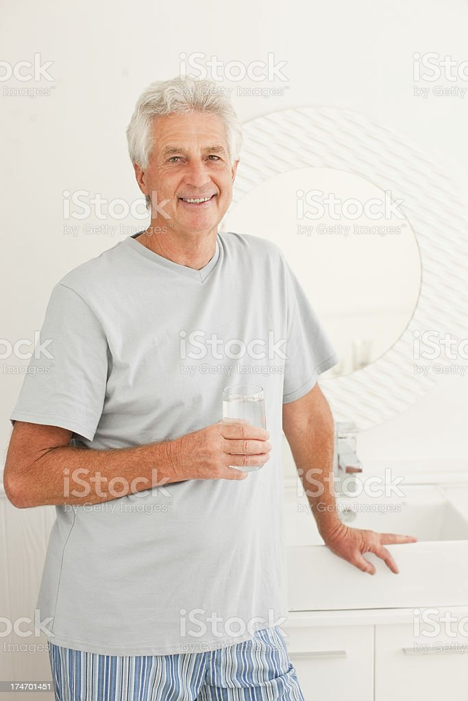 Senior man holding a glass of water royalty-free stock photo