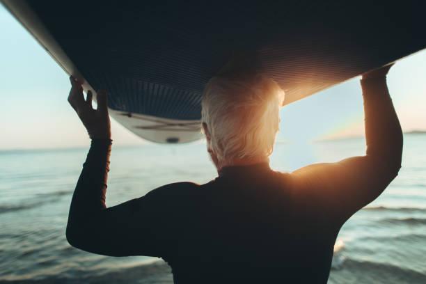 Senior man holding a paddle board stock photo