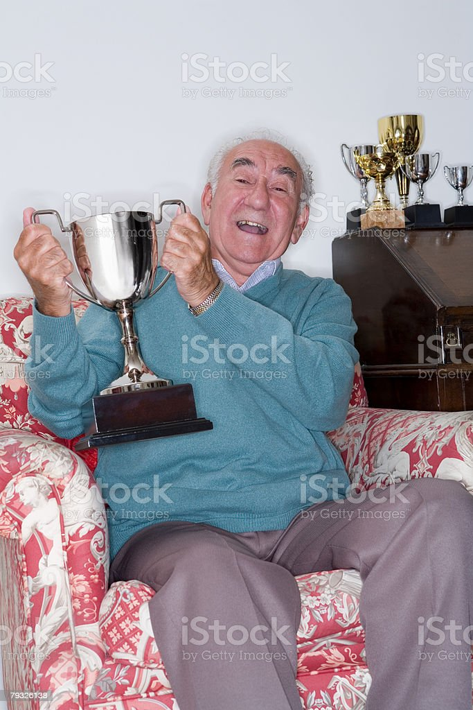 Senior man holding a trophy royalty-free 스톡 사진