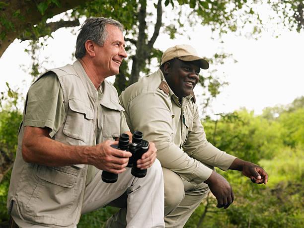 Senior man holding binoculars, on safari with guide, smiling stock photo