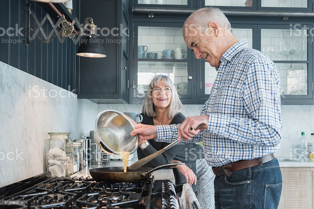Senior man holding bowl making dinner, his wife is watching stock photo