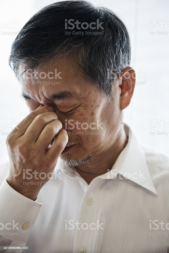 Senior man holding bridge of nose, close-up royalty-free stock photo