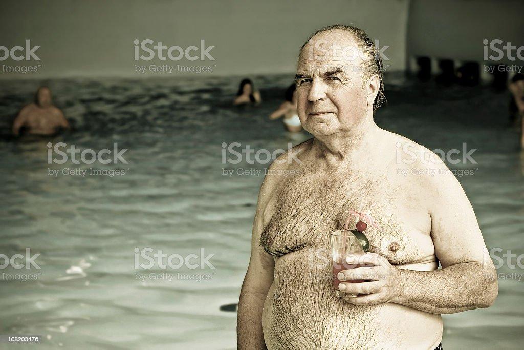 Senior Man Holding Cocktail Drink Near Swimming Pool royalty-free stock photo