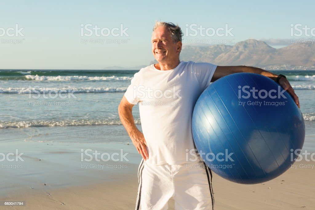 Senior man holding exercise ball while standing at beach foto de stock royalty-free