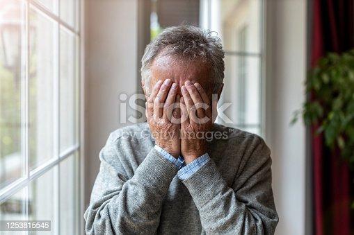 1162960006 istock photo Senior man holding head in hands in despair 1253815545