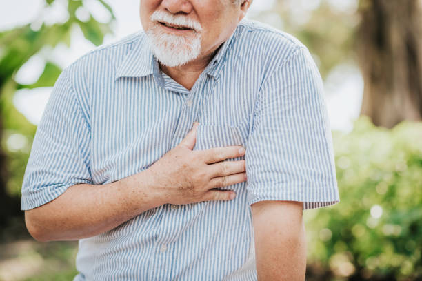 Senior man holding his chest and feeling pain stock photo