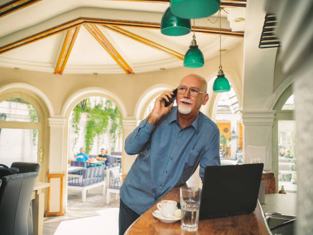 Senior man holding smartphone and using laptop at bar counter Businessman in the cafe, using mobile phone and laptop old man working in a pub stock pictures, royalty-free photos & images