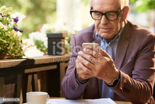 istock Senior Man Holding Smartphone in Cafe 845900426