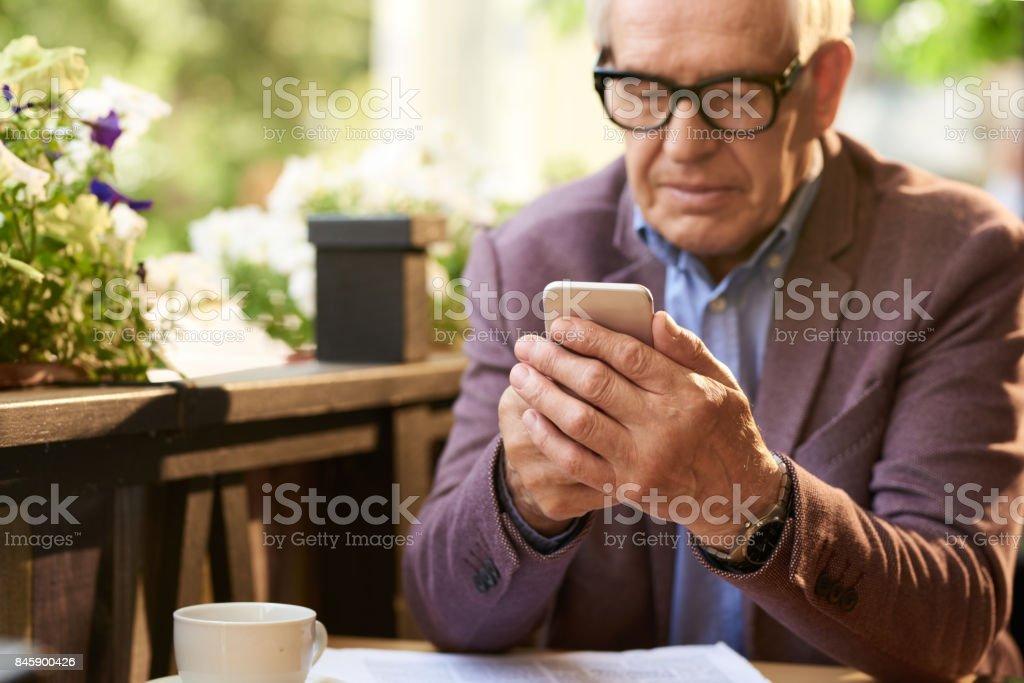 Senior Woman Holding Smartphone im Cafe – Foto