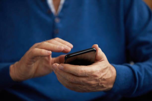 Senior Man Holding Smartphone stock photo