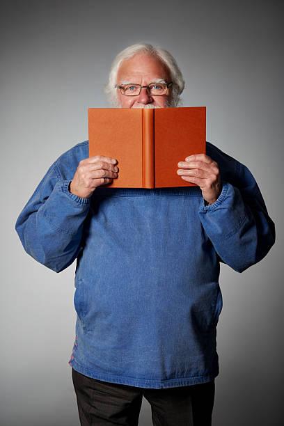 Senior Mann hält ein Buch und Blick in die Kamera – Foto