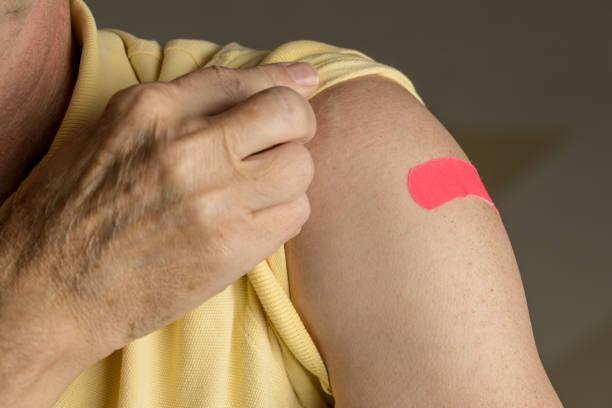 Senior man holding up shirt after flu injection stock photo