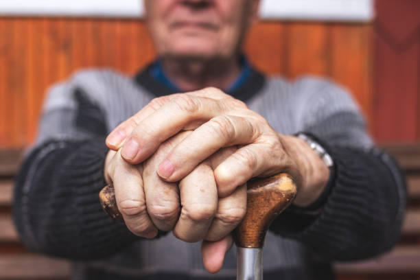 Senior man holding walking cane in his hands stock photo
