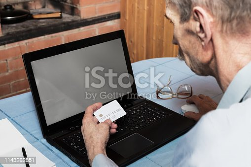 Senior man holding white credit card in front of laptop with blank screen for online shopping