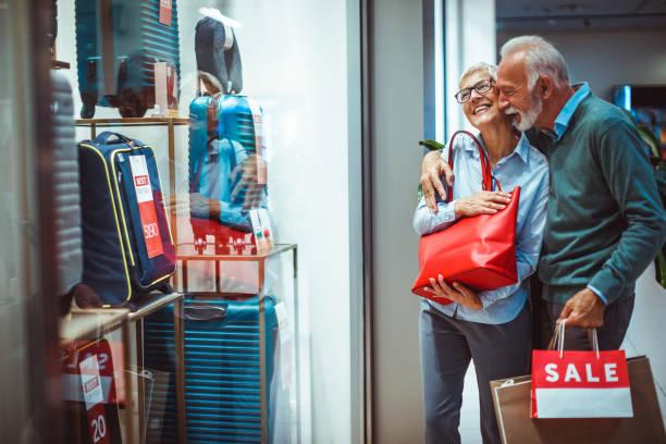 ältere mann umarmt seine partnerin, wie sie mit freude ihre rote handtasche hält kaufte er ihr in der nähe der handtaschen-schaufenster - trolley kaufen stock-fotos und bilder