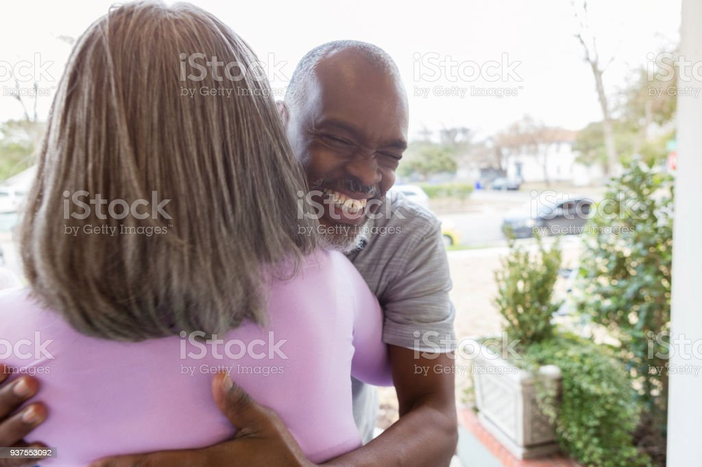 Senior man hugs sister on front porch stock photo