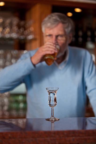 Senior man in a bar drinking beer and Genever​​​ foto