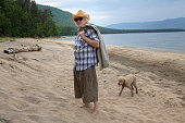 Senior man in a hat walks with a dog along the shore of Lake Baikal