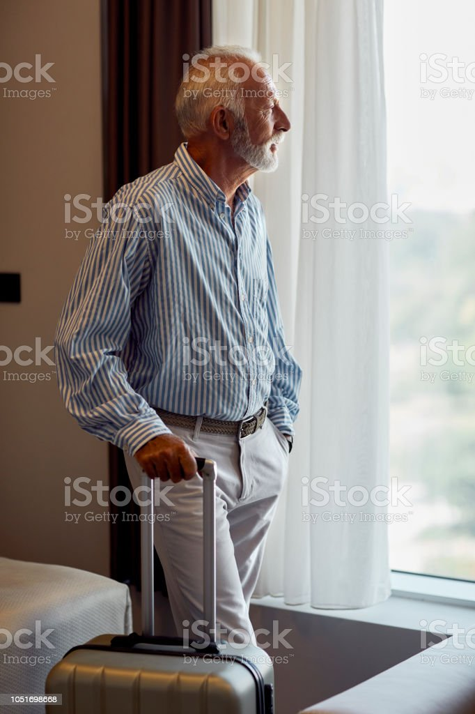 Senior man standing in his hotel room. Looking threw the window and...