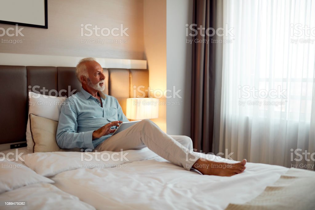 Senior man resting in his hotel room. Looking threw the window and...