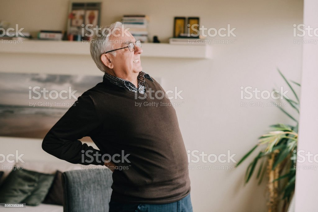 Senior man in a living room having a packpain stock photo