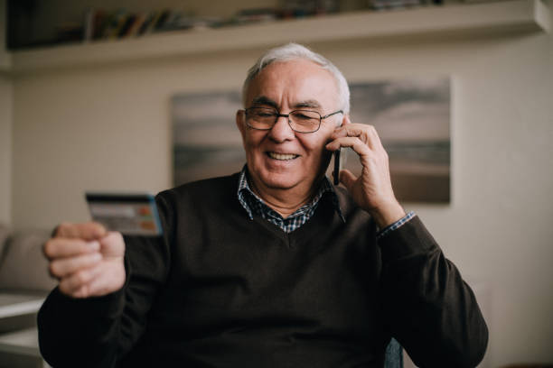 A senior man in a living room talking on a phone and reading his credit card number stock photo
