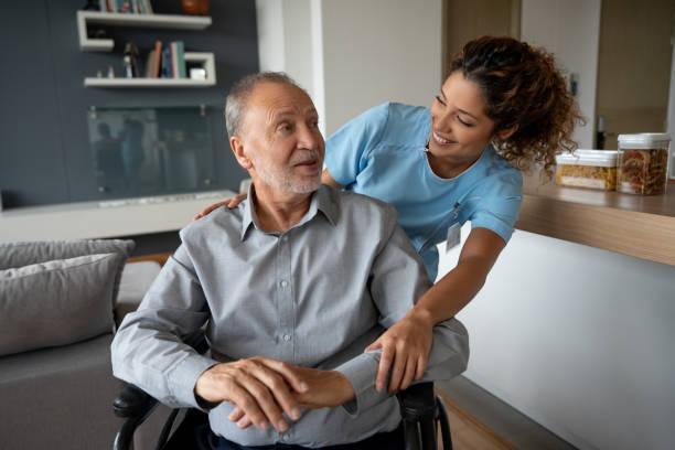 seniorenmann im rollstuhl im gespräch mit seiner hauspflegerin - altenpfleger stock-fotos und bilder