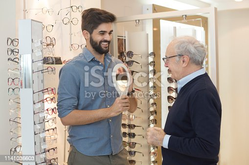 Senior man trying on sunglasses while a young man is helping him. Senior man is about 65 years old and young man is about 30 years old, both Caucasian.
