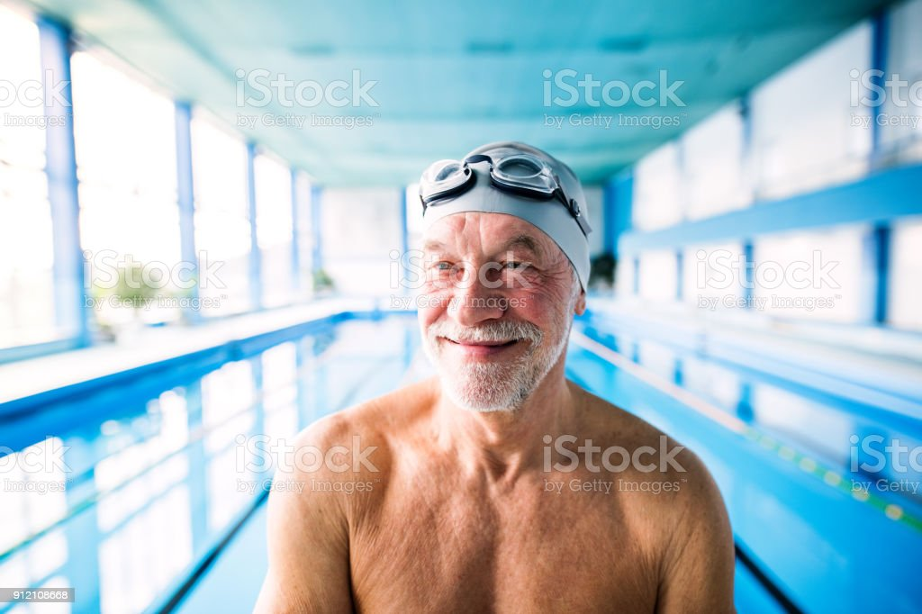 Senior man in an indoor swimming pool. stock photo