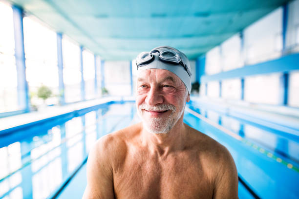 senior man in an indoor swimming pool. - idosos imagens e fotografias de stock