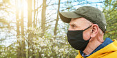 senior man in cap and black face mask stands in garden against blooming trees at back sunlight close side view