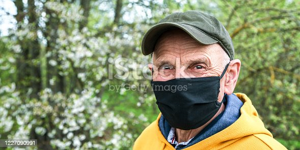 senior man in cap and black medical mask looks ahead standing in garden against blossoming apple trees closeup
