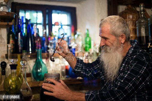 Senior man checking the quality of alcohol liquor with figs. His cellar is full of various bottles of medical liquor, Slovenia, Europe.