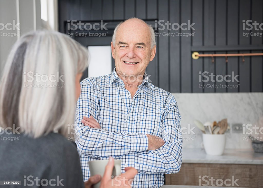 Senior man in checked shirt talking and smiling with wife stock photo