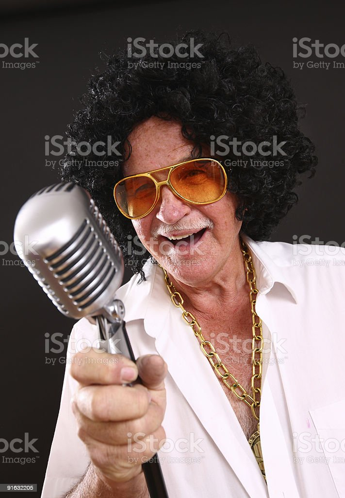 Senior man in costume singing into microphone royalty-free stock photo