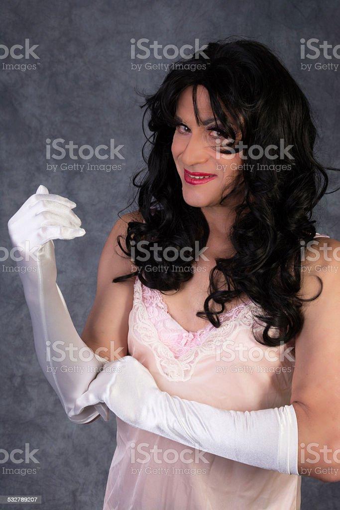 Senior man in drag, wearing lingerie, putting on gloves. stock photo