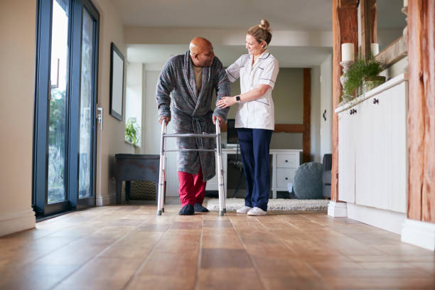 Senior Man In Dressing Gown Using Walking Frame Being Helped By Female Care Worker stock photo