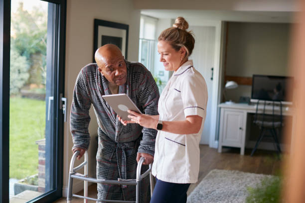 Senior Man In Dressing Gown Using Walking Frame Being Helped By Female Nurse With Digital Tablet stock photo