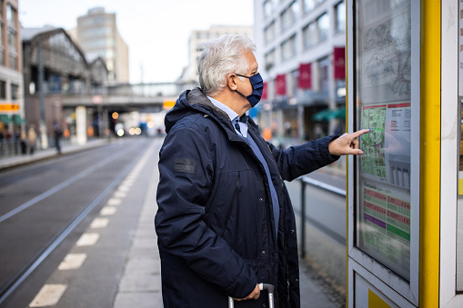 Senior man in face mask looking at the bus line on map