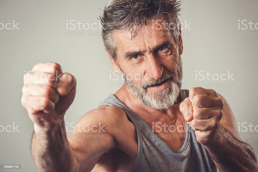 Senior man in fighting position royalty free stockfoto