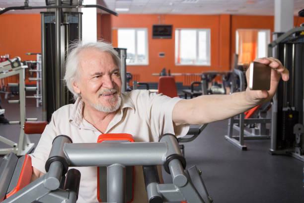 senior man in fitnesscentrum - call center stockfoto's en -beelden
