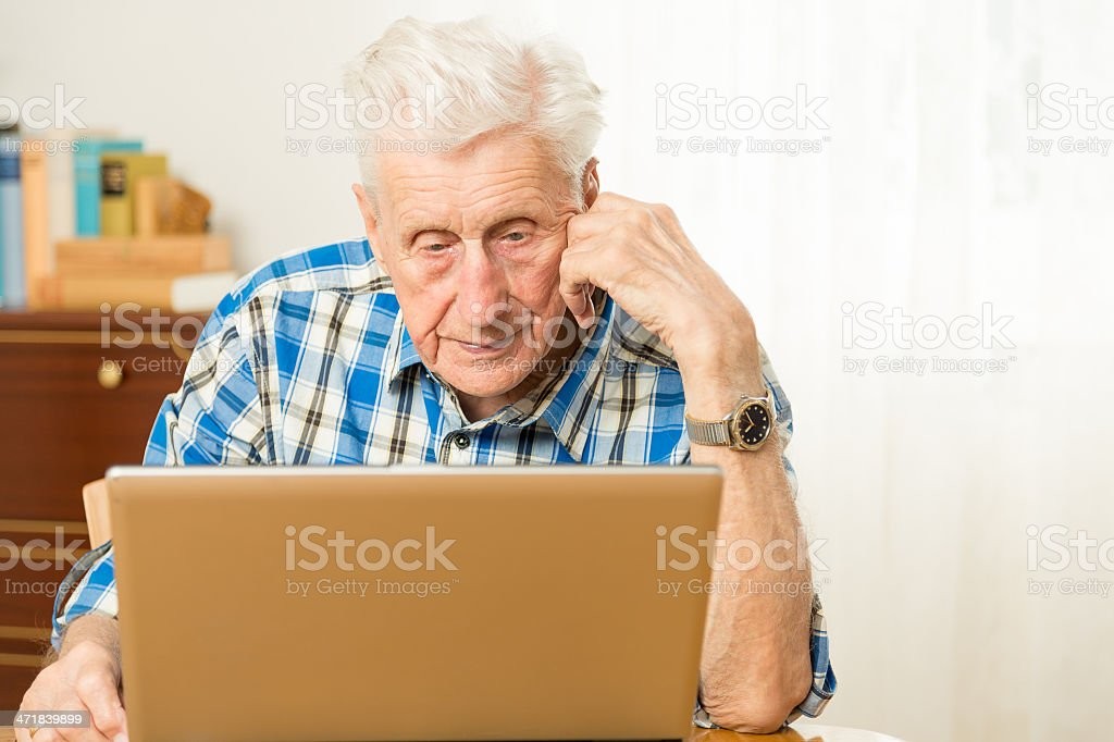 Senior man in front of a laptop computer royalty-free stock photo