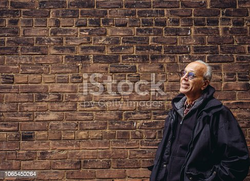 Senior man in fall outfit standing in front of old brick wall.