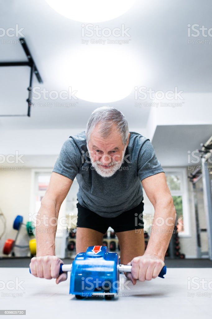 Senior man in gym exercising abs with wheel roller stock photo